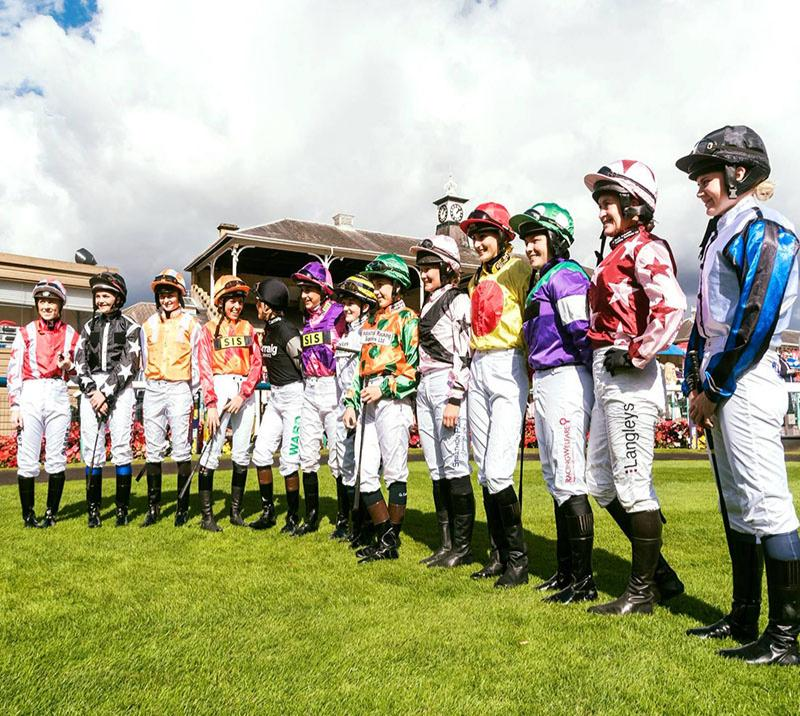 women jockeys standing for photo
