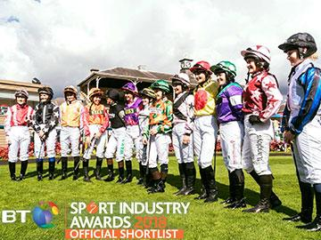 Row of female jockeys posing for a photo.